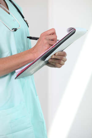 attend: Female nurse holding clipboard and pen