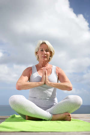 Senior woman in a yoga position photo