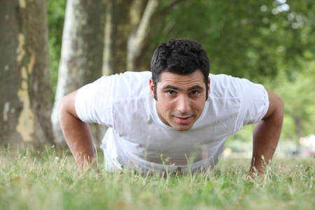 Man doing press ups in the park photo