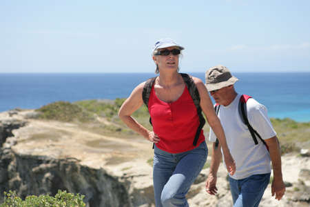 Senior couple hiking by the sea photo