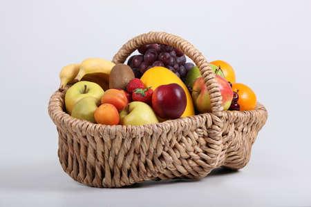 hamper: Wicker basket full of fresh fruit at a slight angle