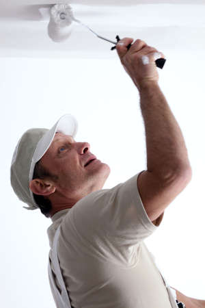 Man painting ceiling with a paint roller photo