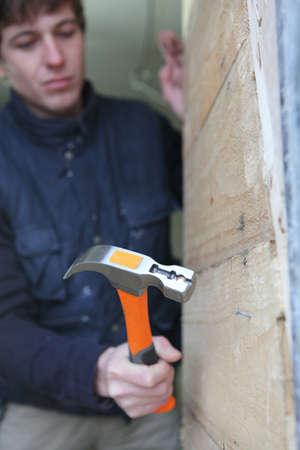 Young carpenter hammering nail into wood photo