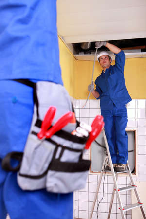 Two electrician repairing ceiling electrics photo