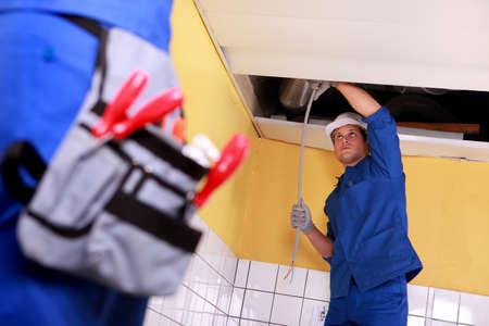 cable red: Dos electricista de trabajo en sistema eléctrico de techo