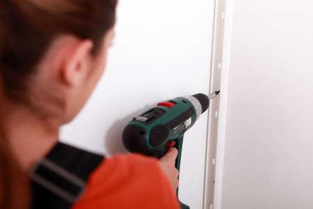 Woman using an electric screwdriver Stock Photo - 22400011