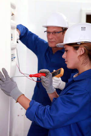 Electrician training his female apprentice photo