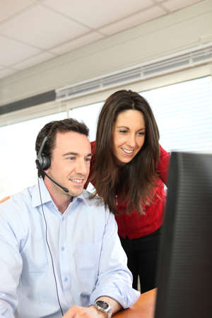 Office couple working at a computer with a headset photo