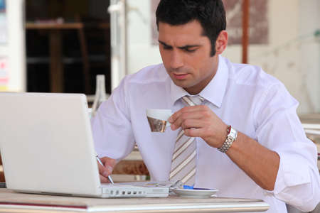 shirtsleeves: Man using  in a cafe