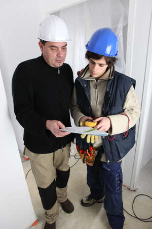 Electrician with young apprentice photo
