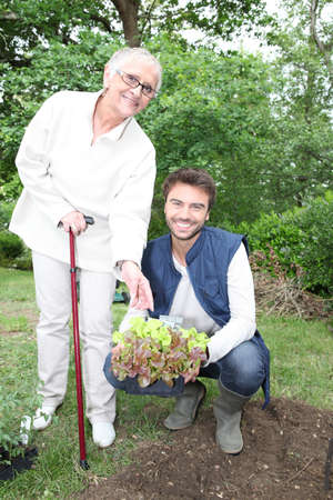 accomplices: young man gardening with older woman
