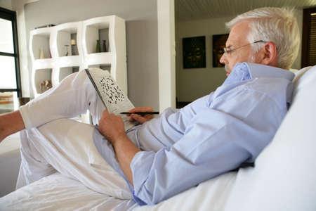 distract: Man doing crossword puzzle Stock Photo