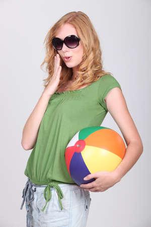 beach ball girl: Studio shot of a cute young redhead with a beach ball