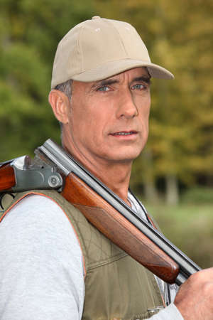 Hunter with rifle on shoulder photo