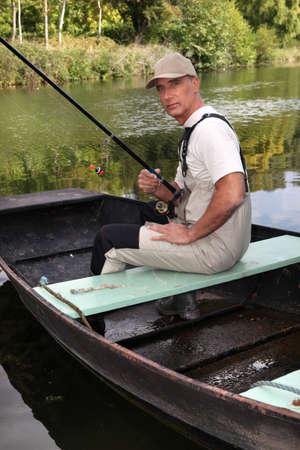 Fisherman sitting in boat photo