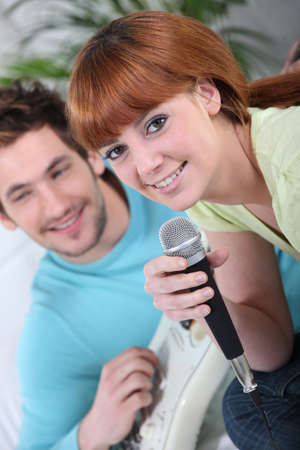 Couple singing and playing the guitar together photo