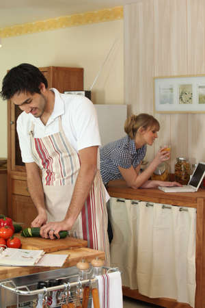 Young couple cooking with a laptop photo