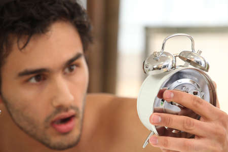 stunned: young man looking stunned at alarm clock