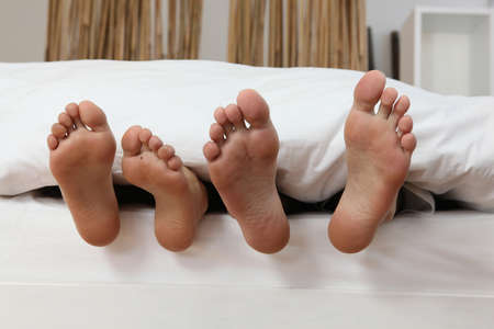 foot cream: male and female feet in bed