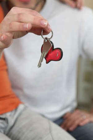 Woman holding a key on a heart keyring photo
