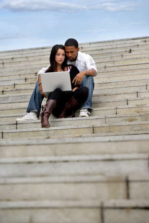 Young couple sitting on steps with a laptop photo
