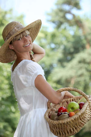Girl with hat and basket of fruit photo