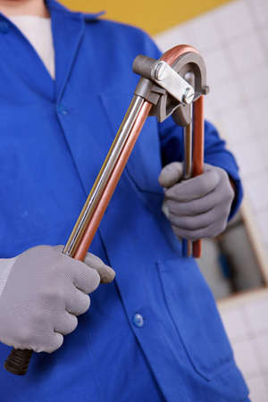 Man bending copper pipe Stock Photo