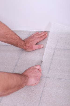 floor covering: Man cutting underlay