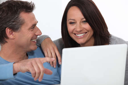 Couple laughing whilst looking at laptop screen photo