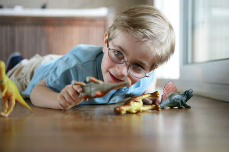 Little boy playing with toy dinosaurs photo