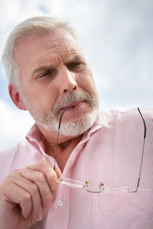 rimless: bearded white-haired senior holding reading glasses Stock Photo