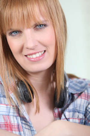 Smiling woman with a pair of headphones round her neck photo