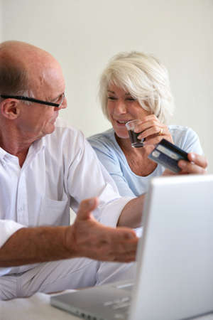 Senior couple booking a holiday on-line photo