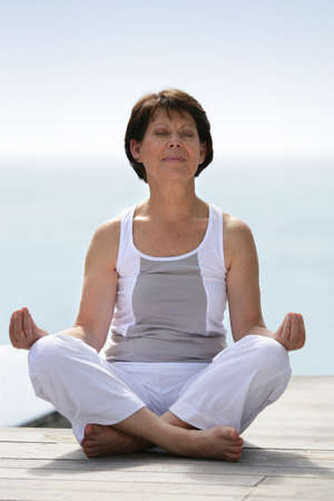 beach mat: Mature woman practicing yoga