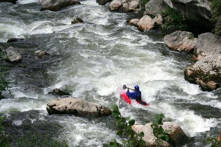whitewater: Man kayaking down rapids