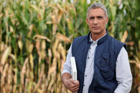 Farmer in a field with a laptop computer photo
