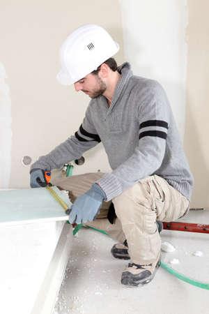 plasterboard: Worker measuring plasterboard