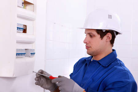 fusebox: Electrician examining a fuse box