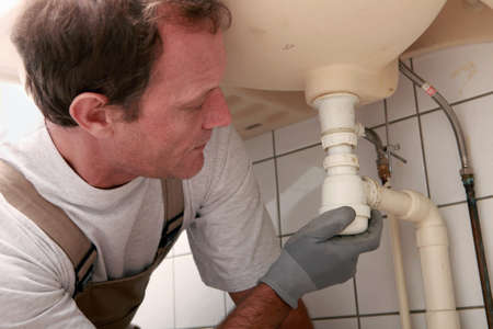 clog: Plumber at a sink Stock Photo