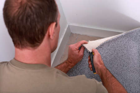 Man cutting carpet to fit a corner of a room photo
