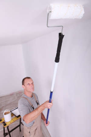 paintcan: Decorator using roller to paint ceiling