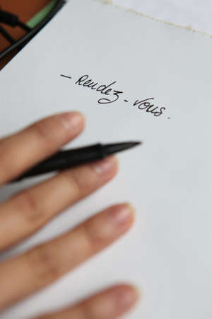 french text: Person writing the words Rendez vous Stock Photo
