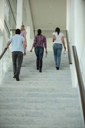 company premises: foursome walking up the stairs Stock Photo