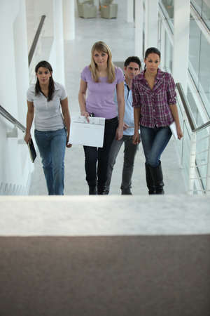 going places: Four people walking up stairs