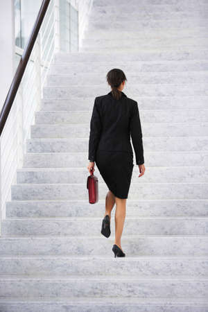 Businesswoman walking up steps photo