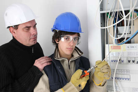 An experienced electrician watching his young apprentice
