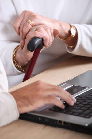descendants: old women hands holding a walking stick and a manly hand typing on a keyboard