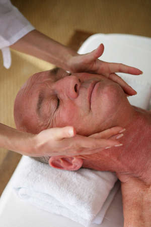 Elderly man receiving a head massage photo