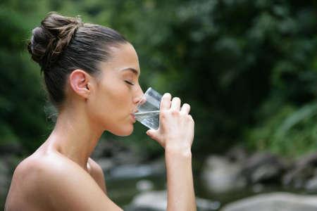 WATER GLASS: Brunette bere un bicchiere d'acqua all'aperto Archivio Fotografico