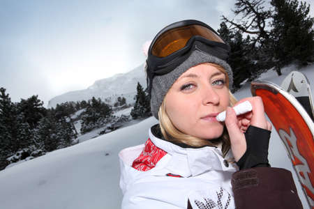 balm: Female snowboarder applying lip balm Stock Photo